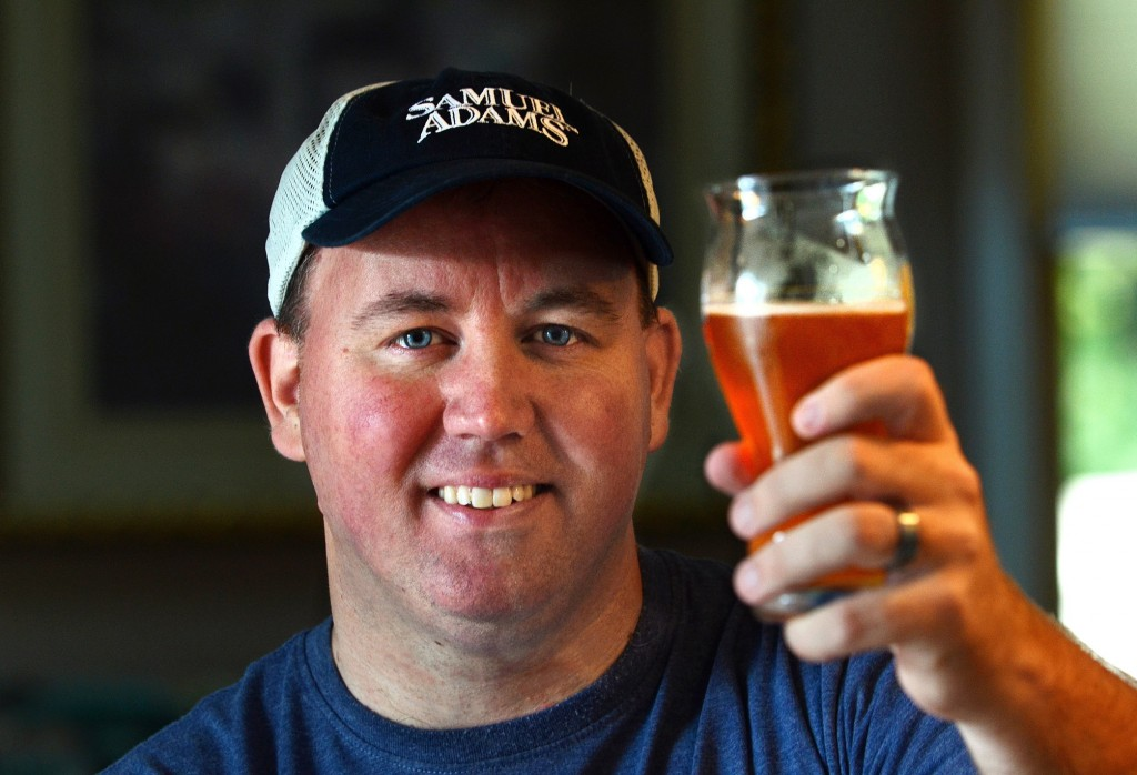 "Todd Ruggere toasts his cause at his home in Weymouth, Mass. He says his fundraising method works because ""People love beer."" He finds people to be ""awesome and generous."""