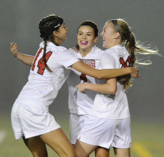 Ashley Perriello of Scarborough is congratulated by Aly Atherton, left, and Morgan Rodway after scoring a second-half goal Wednesday during a 2-2 tie against Windham.