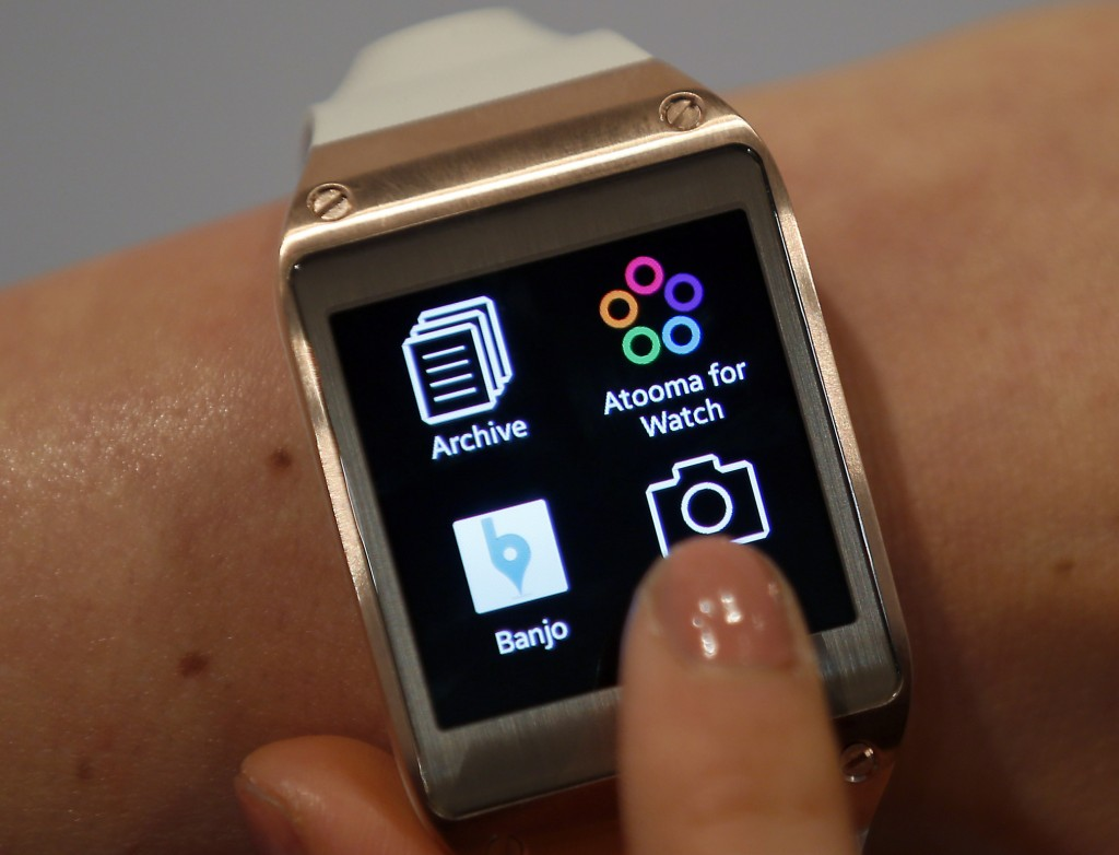 FILE - In this Wednesday, Sept. 4, 2013, file photo, a model touches the screen of a Samsung Galaxy Gear smartwatch in Berlin, Germany. The so-called smartwatch is what some technology analysts believe could become this year's must-have holiday gift.
