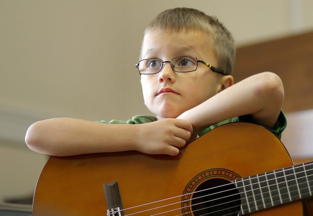 Michael Madden, 5, listens to teacher guitar teacher Don Pride while taking a class at the Portland Conservatory of Music on Tuesday.