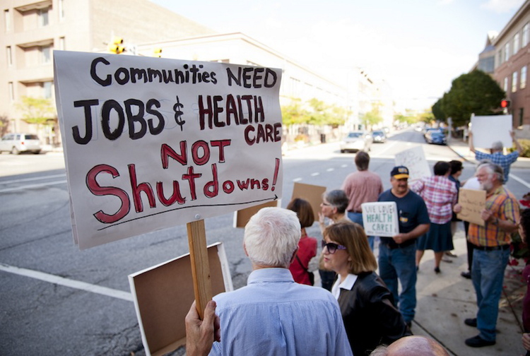 Demonstrators hold signs while protesting outside the Lafayatte, Ind. office of U.S. Representative Todd Rokita, Thursday, Oct. 3, 2013. They were protesting the government shutdown and Rokita's stance on it.