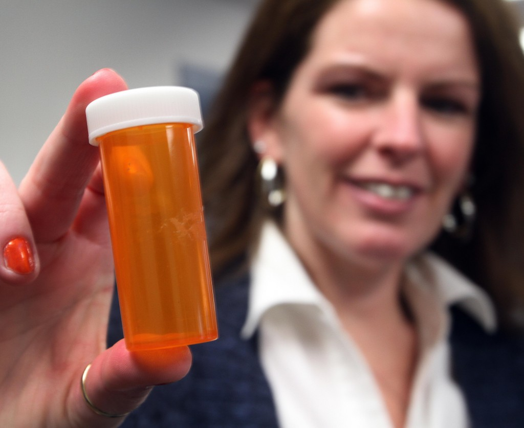 Novelty pill bottles like this one displayed by Celeste Clark, director of the Raymond (N.H.) Coalition for Youth, will no longer be used as promotional items by an online firm.