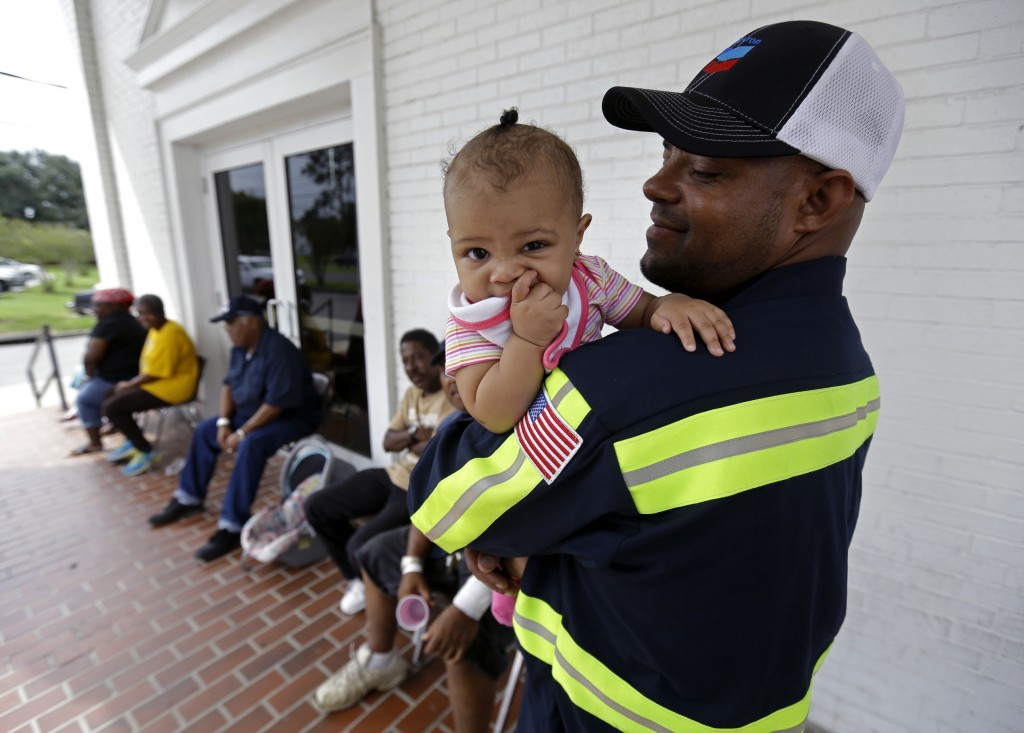 Gregory Ragas, of Davant, La., holds his daughter Jasmine Ragas, 1 year, at an evacuation shelter in Belle Chasse, La., in anticipation of Tropical Storm Karen, Saturday, Oct. 5, 2013. The East Bank of Plaquemines Parish has been under a mandatory evacuation, which has been downgraded to a voluntary evacuation. in Belle Chasse, La., Saturday, Oct. 5, 2013.