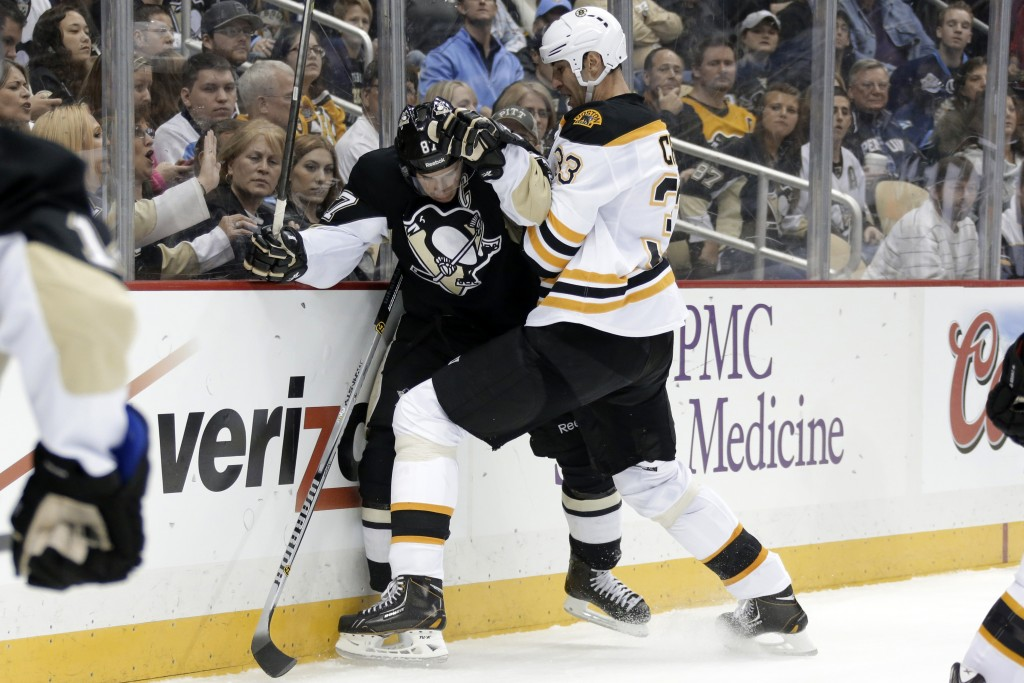 Zdeno Chara of the Bruins slams Pittsburgh's Sidney Crosby into the boards during Wednesday's game in Pittsburgh. The Penguins won, 3-2.