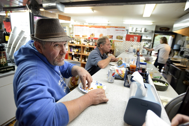 Georgetown selectman Bill Plummer is among the patrons at Georgetown Country Store on Monday, Oct. 7, 2013 to talk about resident Leon Kelley after he was fatally shot at Brown's Bee Farm in Cumberland yesterday.