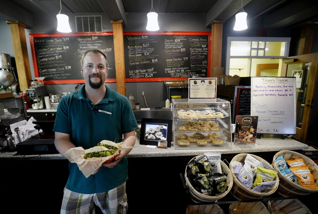 "Mark Claussen of Saco Island Deli in Saco shows off a ""Mainah,"" one of the deli's specialty sandwiches."