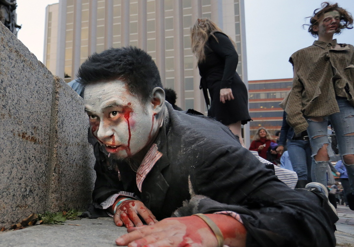 Brian Noyes of Portland, dressed as a vampire zombie, crawls along the base of the monument in Monument Square on Wednesday. Noyes was part of a flash mob performance that attracted about 300 spectators.
