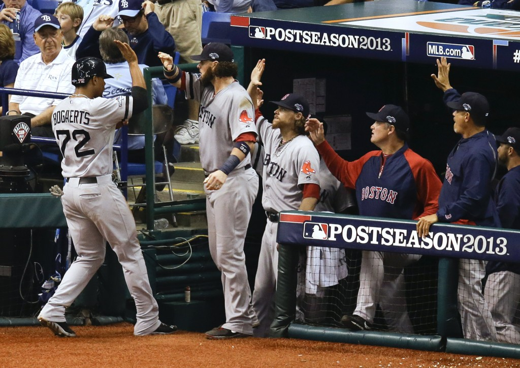 Boston Red Sox's Xander Bogaerts trades high-fives with teammates in the dugout after he scored in the seventh inning on a wild pitch by Tampa Bay Rays relief pitcher Joel Peralta.