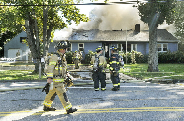 Firefighters extinguish a blaze at a home on Park Road in Westbrook on Tuesday. The fire started in a generator that had been turned on after a nearby car accident knocked out power.
