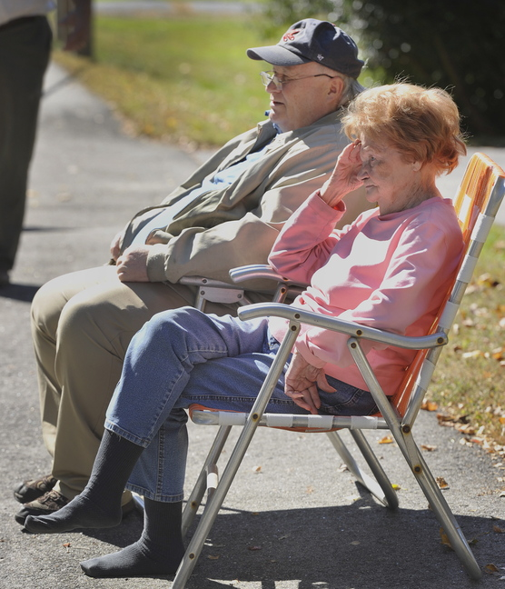 Kathryn Crowley and her son Daniel Crowley watch from across the street Tuesday as firefighters put out a fire at their home.