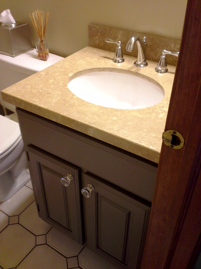 New doors, a new light brown travertine vanity top with an integrated sink, a new faucet and a couple of glass knobs make for a whole new vanity.