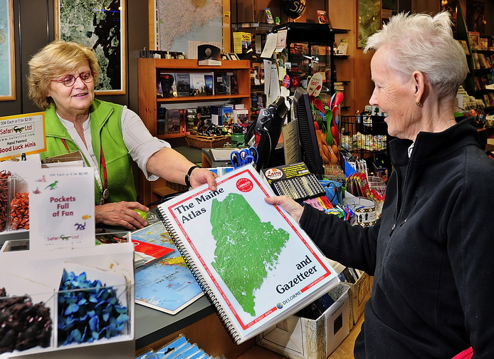 Judy Gilbert, DeLorme map store associate, sells the latest edition of the Maine Atlas & Gazetteer to Anne Hess of Stillwater. The Atlas & Gazetteers and other paper map products still account for about 15 to 20 percent of the company's product sales, according to Jim Shillings, vice president of commercial products.