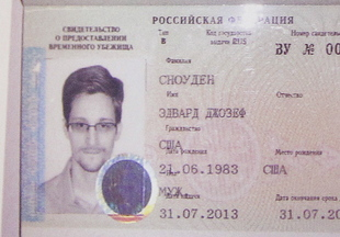 Former NSA contractor and fugitive Edward Snowden, shown in his new refugee documents, is adjusting to Russia, say four Americans who visited him Wednesday night. Snowden's father has also arrived to visit his son.