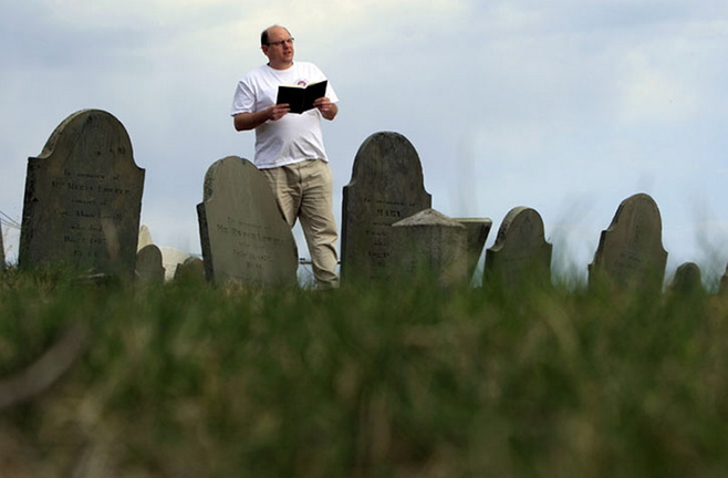 Walter Skold of Freeport reads a Henry Wadsworth Longfellow poem in Portland's Eastern Cemetery in this April 2010 photo.