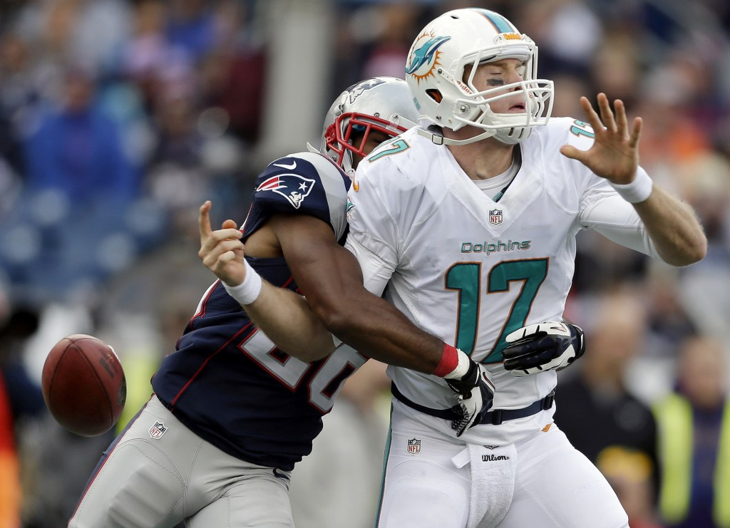 New England Patriots defensive back Logan Ryan, left, strips the ball from Dolphins quarterback Ryan Tannehill in the second half Sunday at Foxborough, Mass.