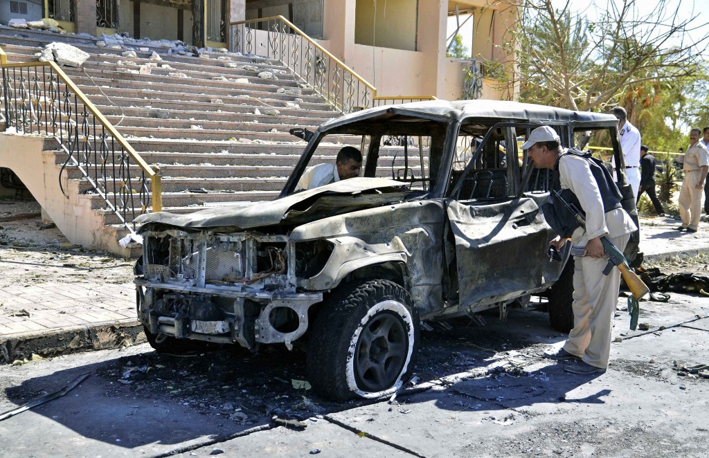 Egyptian security forces inspect the site of a suicide car bombing on a security headquarters in the southern Sinai town of el-Tor, Egypt, on Monday.