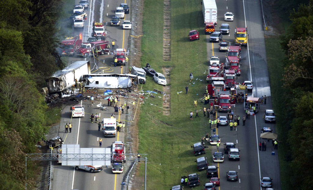 In this aerial photo, emergency workers respond to a crash involving a passenger bus, a tractor-trailer and an SUV near Dandridge, Tenn., on Wednesday. Authorities said the bus, carrying members of a North Carolina church group, veered across the highway median and crashed into the other vehicles in a fiery wreck that killed eight people.