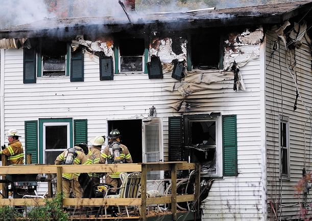 Staff photo by Joe Phelan Firefighters work to put out a house fire at 119 Granite Hill Road in Manchester on Saturday. One man died in the blaze.