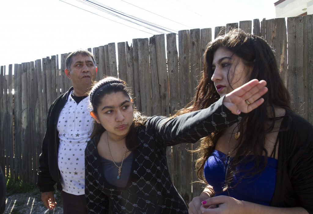Leonarda Dibrani, 15, center, with her sister Maria, 17, and her father, Resat Dibrani, gestures in front of a shelter house in the northern town of Mitrovica, Kosovo, on Friday. The family was expelled from France as illegal immigrants last week and Leonarda Dibrani, taken by police from a school field trip last week, shocked many. Thousands of high school students protested in Paris angry at the expulsion of immigrant children and families like the Dibrani family. The demonstration came as the government was finalizing a report on Friday into the treatment of a 15-year-old girl taken by police from a school field trip, then deported to Kosovo with her family as illegal immigrants.