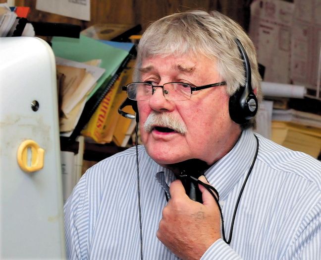 Morning Sentinel reporter Doug Harlow speaks on the phone while using an electronic voice box device.