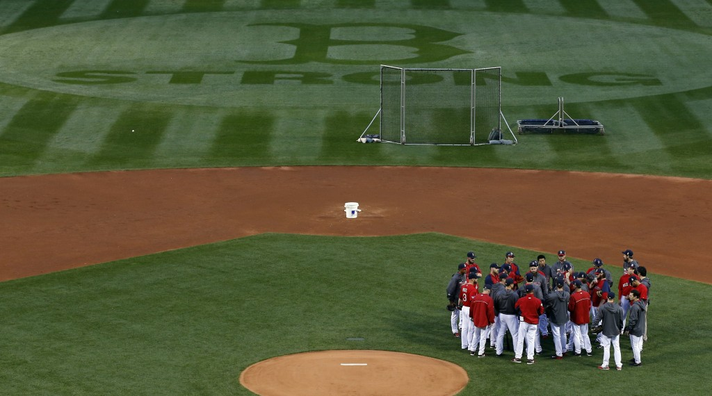 Boston Red Sox players and coaches gather in the infield before a workout at Fenway Park Tuesday.