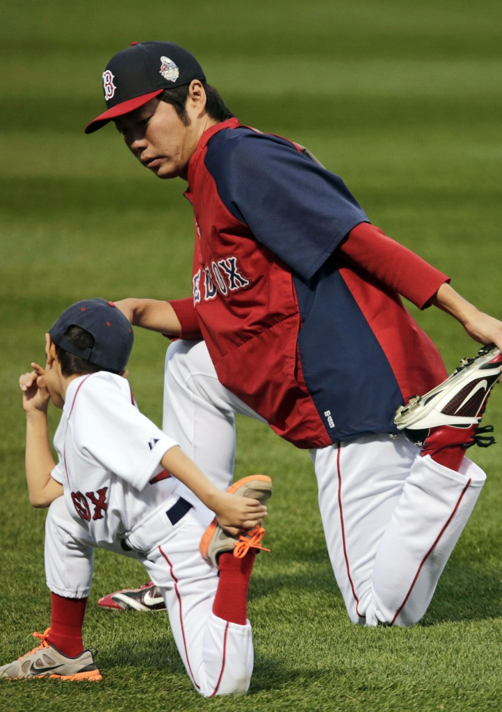 Boston Red Sox closer Koji Uehara stretches with his son Kazuma during a workout out at Fenway Park Tuesday. Uehara, in his first season with Boston, was MVP of the ALCS.