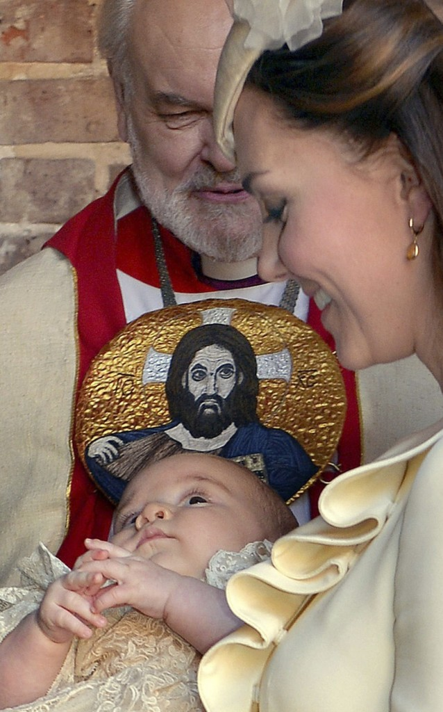 Kate, Duchess of Cambridge, holds Prince George after his christening in London as Bishop of London Richard Chartres looks on.