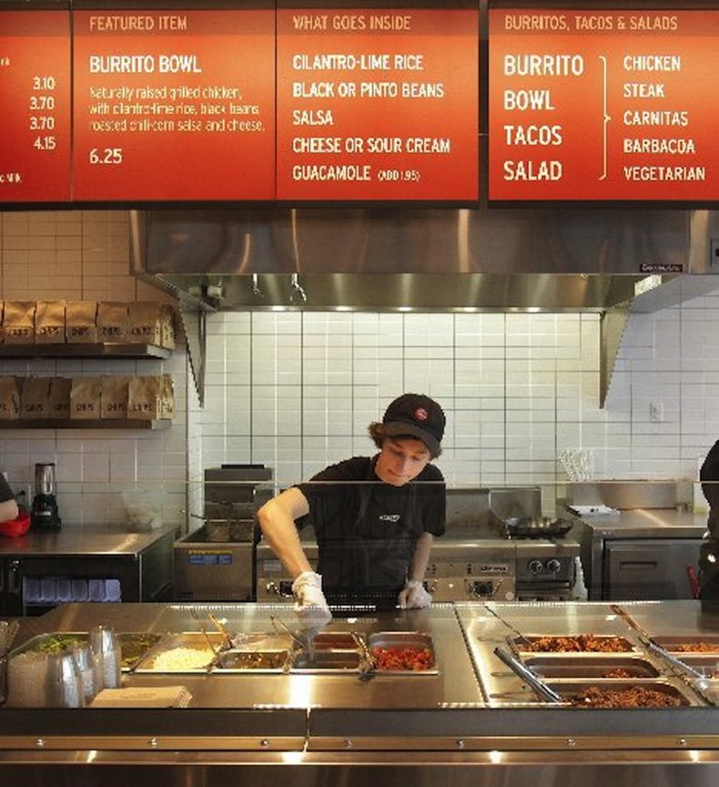 In this December 2010 file photo, Kyle Braley stirs a tomatillo green chili salsa at Chipotle Mexican Grill in South Portland. The popular restaurant chain, which serves naturally-raised beef, chicken and pork, has seen its profits skyrocket as more Americans look for slightly higher-quality fast food.