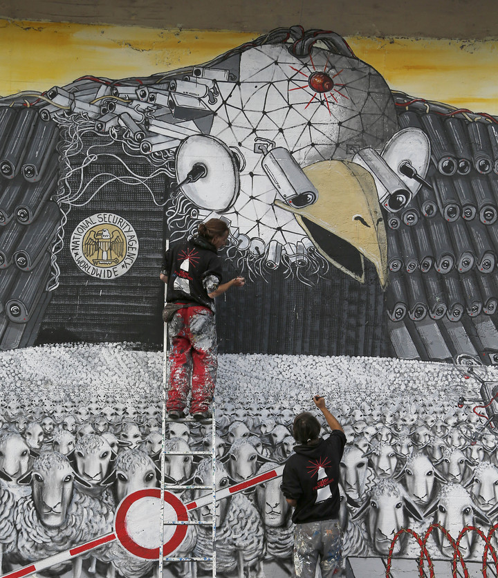 Artists A.Signl, left, and B. Shanti of the artist group Captain Borderline paint their mural 'Surveillance of the fittest' at a wall in Cologne, Germany, Thursday. The painting, showing an American bald eagle with surveillance cameras watching a herd of sheep, is aimed at drawing attention to the spying program of the American National Security Agency.