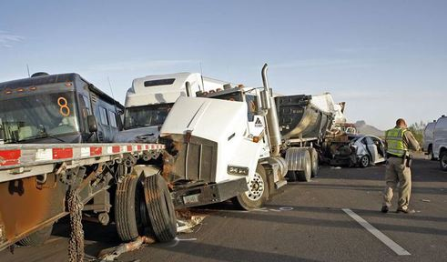 Public safety officers investigate a 19-vehicle pileup caused by a dust storm Tuesday on Interstate 10 south of Casa Grande, Ariz. Three people were killed and 12 wee injured.