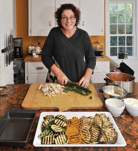 Cooking instructor Christine Burns Rudalevige chops kale and mushrooms in her Brunswick kitchen for her No-Noodle Vegetable and Turkey Lasagne. She created the recipe to use vegetables such as eggplant, zucchini or butternut squash that can be cut round and flat and grilled, in place of noodles, and added turkey and cheeses.