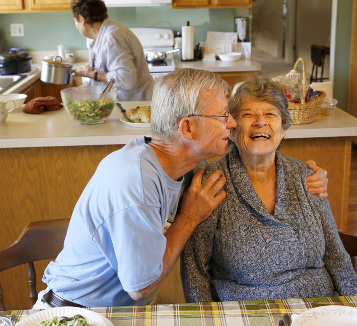 Bill Kelly, 64, gives roommate Jackie Kindl, 81, a hug at lunch in the house they share with three other seniors in Lombard, Ill.