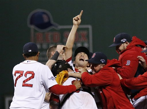 Boston Red Sox relief pitcher Koji Uehara, center, celebrates with teammates after the Red Sox beat the Detroit Tigers in Game 6 of the American League Championship Series on Saturdayin Boston.