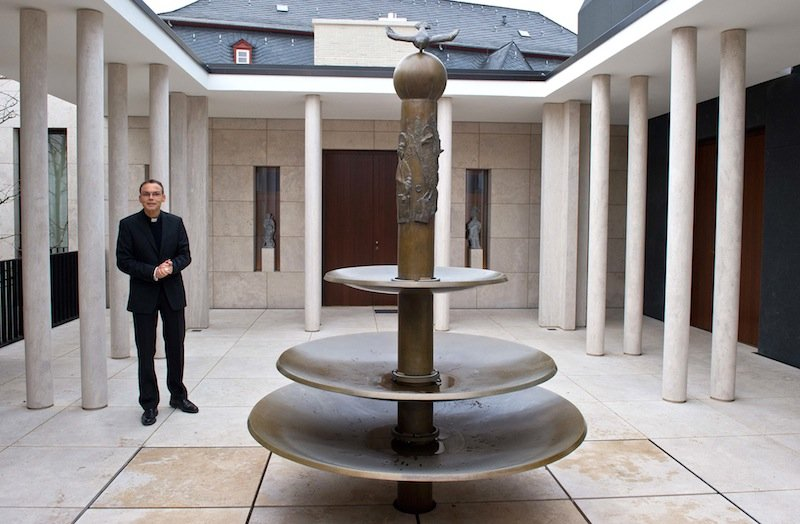 """In this Dec. 3, 2012 file picture Franz-Peter Tebartz-van Elst, Bishop of Limburg , Germany stands in the atrium of the chapel at the Bishop's residence in Limburg, Germany. Pope Francis temporarily expelled the German bishop from his diocese on Wednesday Oct. 23, 2013 because of a scandal over a 31-million-euro ( US dlrs 42 million) project to build a new residence complex, but refused popular calls to remove him. The Vatican didn't say how long Bishop Franz-Peter Tebartz-van Elst would spend away from the diocese of Limburg. But it said Limburg's newly named vicar general, the Rev. Wolfgang Roesch, would run the diocese during Tebartz-van Elst's """"period of time away. Luxus;Va;Limburg;Religion;Bischof;Kirche;Dom;Franz-Peter Tebartz-van Elst"""