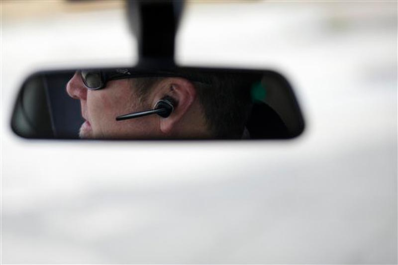 In this December 2011 file photo, Dan Johnson uses a hands-free device to talk on a cellphone while driving. Maine law enforcement officers will have to get search warrants to gather information from cellphones including voicemails, text messages or location data, under two laws that will take effect Wednesday.