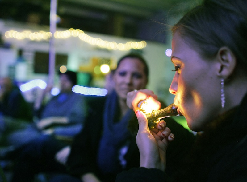 In this in Dec. 31, 2012 file photo, Rachel Schaefer of Denver smokes marijuana on the official opening night of Club 64, a marijuana-specific social club, where a New Year's Eve party was held, in Denver. A clear majority of Americans now support legalizing marijuana for the first time since Gallup began tracking the issue 40 years ago.