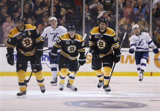Boston Bruins' Patrice Bergeron, Torey Krug and Adam McQuaid skate to the bench in front of Tampa Bay Lightning's Richard Panik, of Slovakia, and Tyler Johnson after Bergeron's goal in the third period Thursday. The Bruins won 3-1.