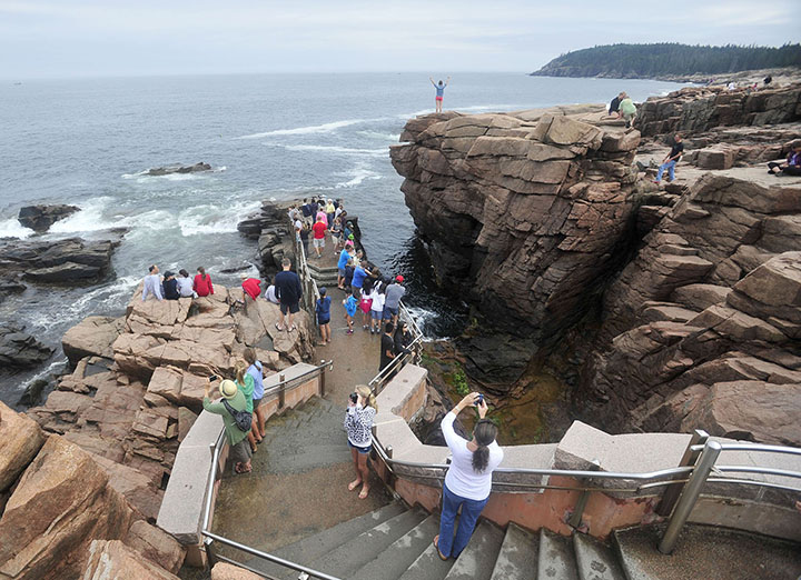 Crowds of people gather around Thunder Hole at Acadia National Park in Bar Harbor in July. As congressional leaders raced to seal a deal that would reopen the government, lawmakers from both parties jabbed at one another Wednesday over who was to blame for the most high-profile casualties of the 16-day shutdown: the national parks.