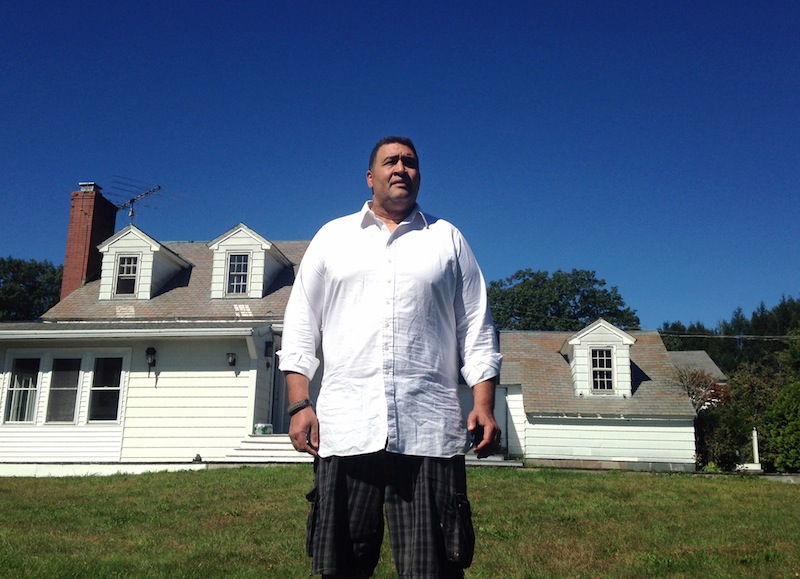 Former NFL offensive lineman Brian Holloway stands in front of his rural vacation home on Sept. 18, 2013, in Stephentown, N.Y. The home was trashed during a Labor Day weekend party attended by an estimated 200 to 400 teenagers.