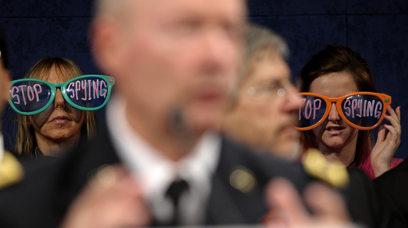 Protesters wearing oversized glasses listen as NSA Director Gen. Keith Alexander testifies Tuesday in Washington.