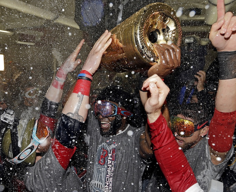 Boston Red Sox's David Ortiz holds up a large bottle of Champagne as he celebrates with teammates after Game 6 of baseball's World Series against the St. Louis Cardinals Thursday, Oct. 31, 2013, in Boston. The Red Sox won 6-1 to win the series. Ortiz was names the series MVP.