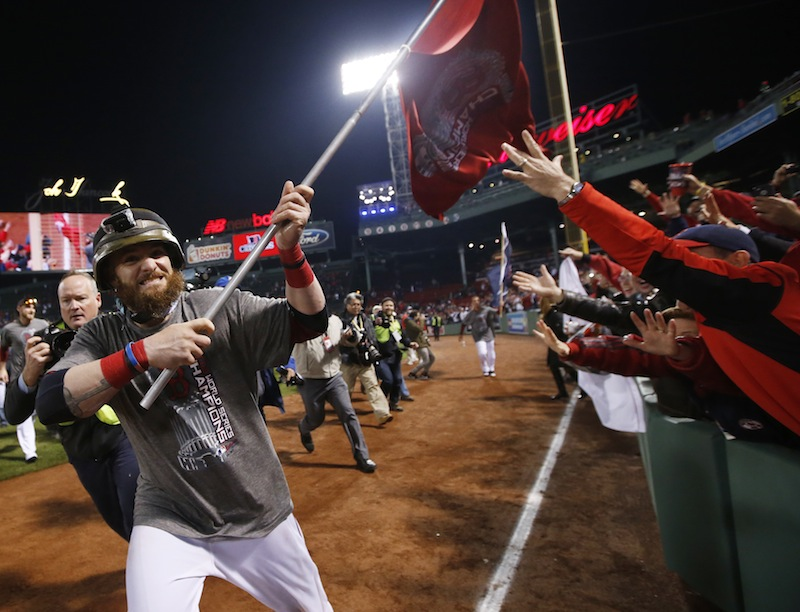 Boston Red Sox left fielder Jonny Gomes runs with a championship flag after defeating the St. Louis Cardinals in Game 6 of baseball's World Series Thursday, Oct. 31, 2013, in Boston. The Red Sox won 6-1 to win the series. MLB