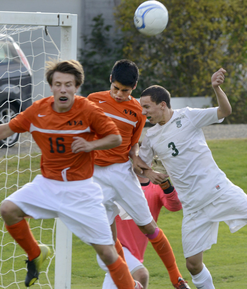 Xander Bartone of North Yarmouth Academy heads the ball away from the net Wednesday between his teammate, Jeremy Thelven, 16, and Harry Baker-Connick of Waynflete.