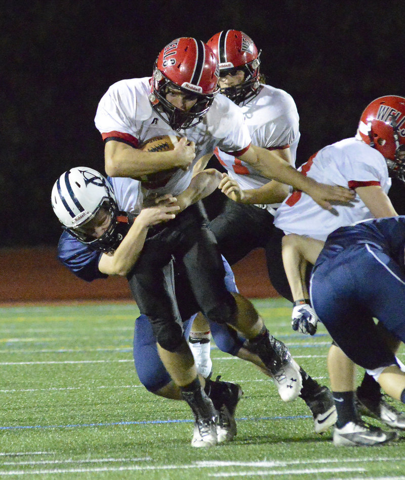 Chris Carney of Wells is pulled down by Yarmouth's Lucas Uhl during their Western Class C football game Friday in Yarmouth. Carney returned a free kick after a safety for the go-ahead touchdown in Wells' 22-15 victory.