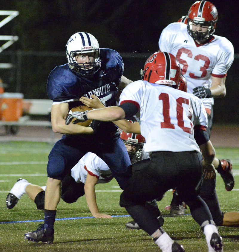 Yarmouth running back Matt Woodbury looks for room to run as Jake Moody and other Wells defenders move in for the tackle.