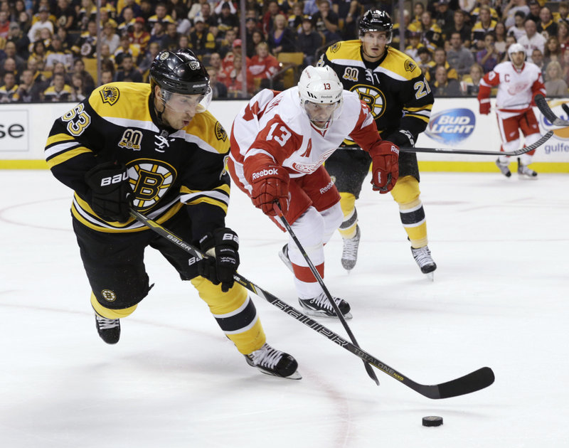 Bruins forward Brad Marchand keeps the puck away from Detroit's Pavel Datsyuk during first-period action of Saturday night's 4-1 victory in Boston. Marchand scored the winning goal in the second period.