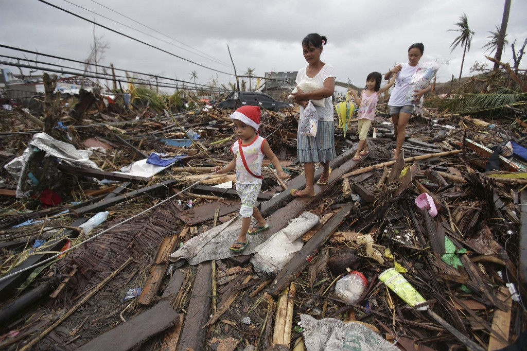Survivors walk in typhoon-ravaged Tacloban city, Leyte province, central Philippines on Tuesday. The Philippines emerged as a rising economic star in Asia but the trail of death and destruction left by Typhoon Haiyan has highlighted a key weakness: fragile infrastructure resulting from decades of neglect and corruption.
