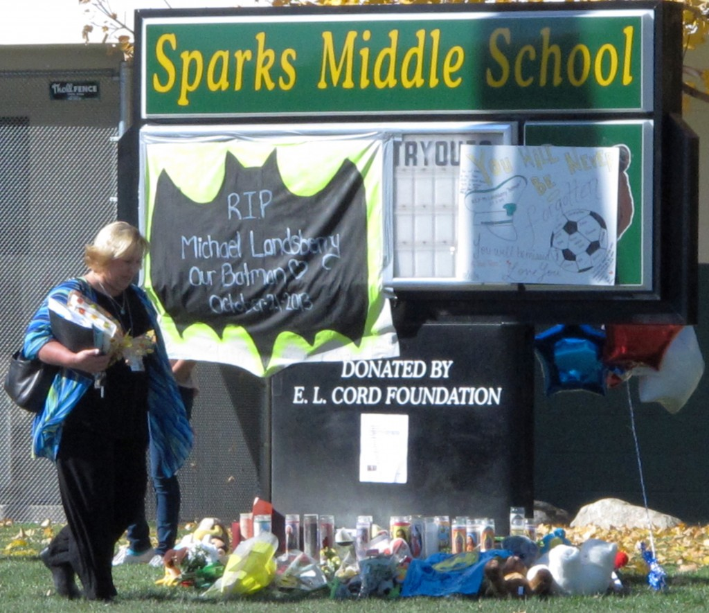 In this Oct. 23, 2013, photo, Washoe County School Board President Barbara Clark walks past a makeshift memorial in front of Sparks Middle School in Sparks, Nev., where math teacher Michael Landsberry was killed and two students wounded before a 12-year-old gunman killed himself.