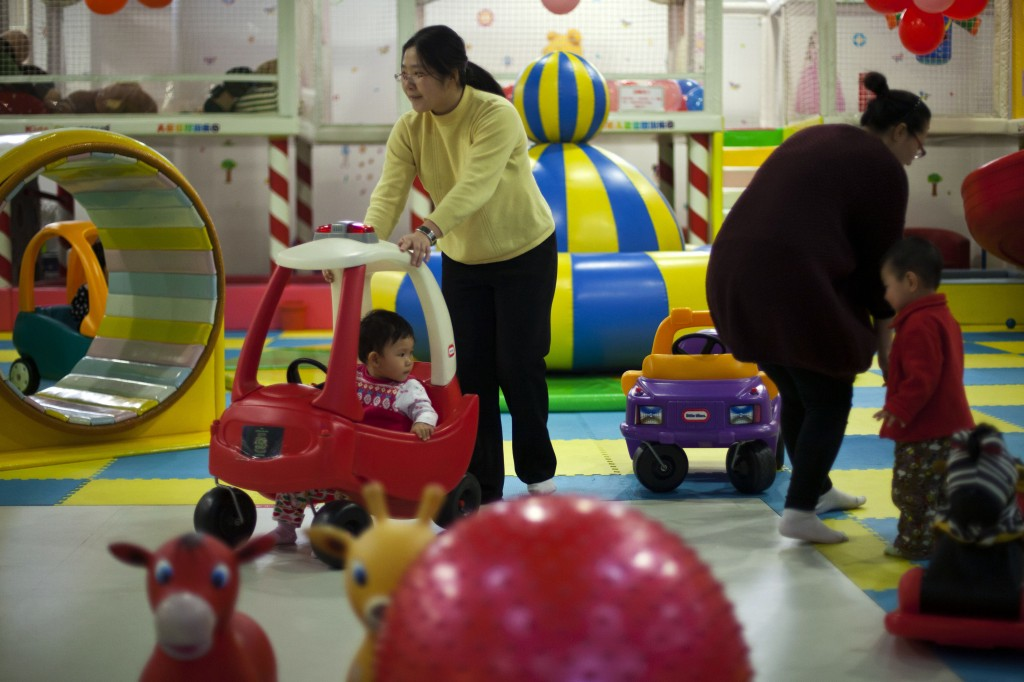 Parents play with their children at a kids' play area in a shopping mall in Beijing last January. With China's one-child policy, birth rates plunged from 4.77 children per woman in the early 1970s to 1.64 in 2011, according to estimates by the United Nations.
