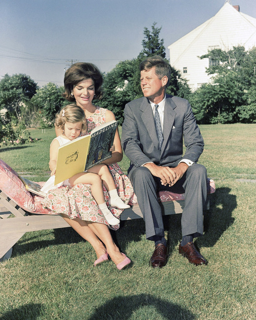 In this July 25, 1960 file photo , Sen. John F. Kennedy, D-Mass., sits with wife, Jacqueline, as she reads to their daughter, Caroline, at Hyannis Port, Mass.